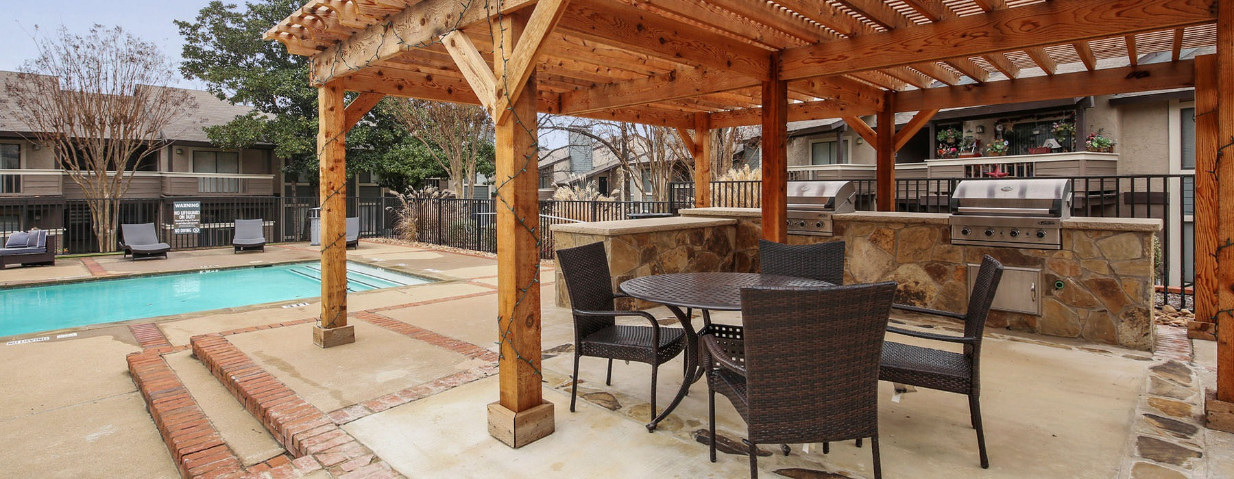 pergola covered grilling stations and picnic area near pool