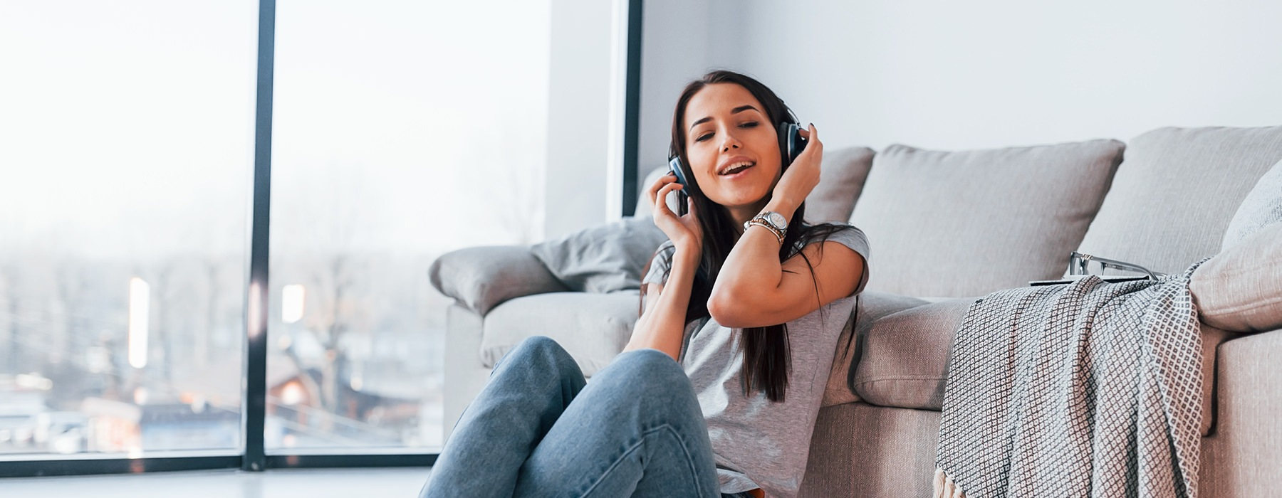 woman with headset on listens to music as she sits against her couch on living room floor